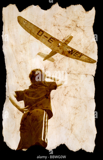 A young boy watching a plane fly over. - Stock-Bilder