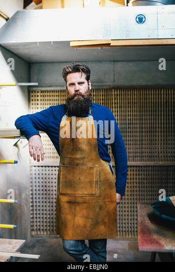 Portrait of mid adult craftsman leaning on shelf in organ workshop - Stock Image