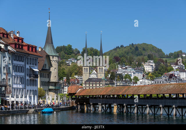 Chapel Bridge (Kapellbrucke) and the Hofkirche in the city of Lucerne (Luzurn) in Switzerland. The Hofkirche or - Stock Image