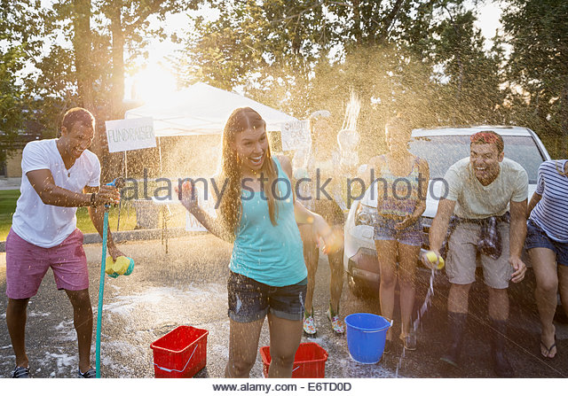 Man spraying woman with hose at car wash - Stock Image