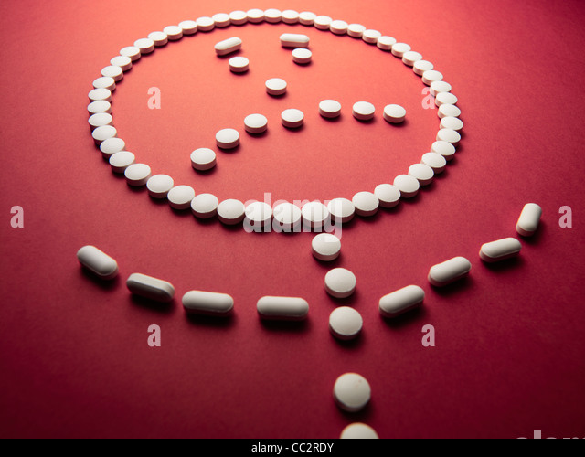 unhappy face made out of pills and drugs - Stock Image