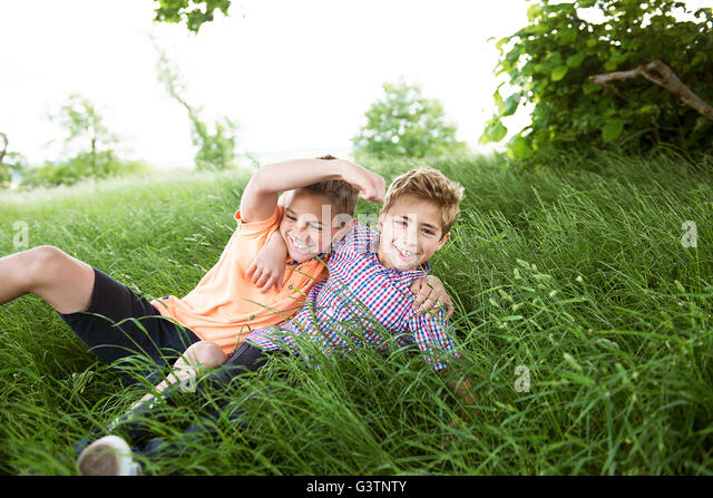 Two boys sitting and playing in long grass in the countryside. - Stock Image