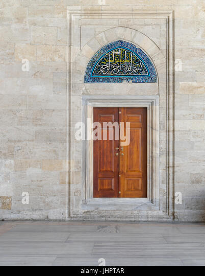 Wooden engraved door on stone wall and tiled marble floor, Sulaymaniye Mosque, Istanbul, Turkey - Stock Image