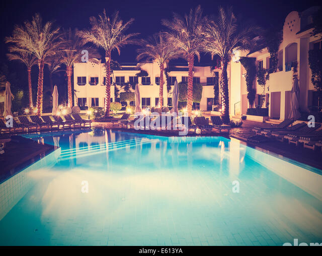 Retro vintage style picture of pool side of hotel at night. - Stock Image