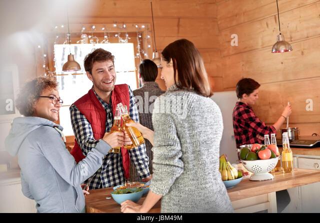 Friends toasting beer bottles in cabin kitchen - Stock-Bilder