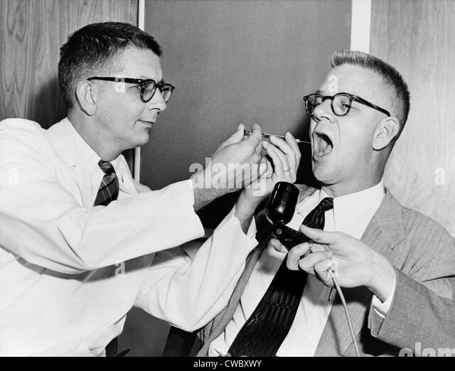 Dr. Harry L. Williams squirts LSD from a syringe into the mouth of Carl Curt Pfeiffer, M.D., Ph.D. (1908–1988) at - Stock Image