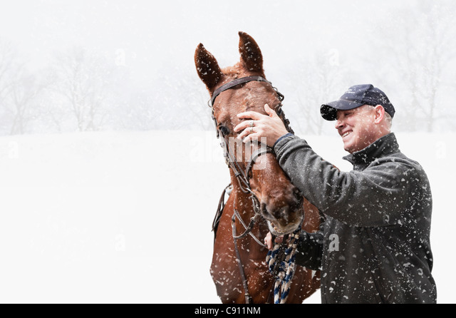 USA, Illinois, Metamora, Smiling mature man with horse during blizzard - Stock Image