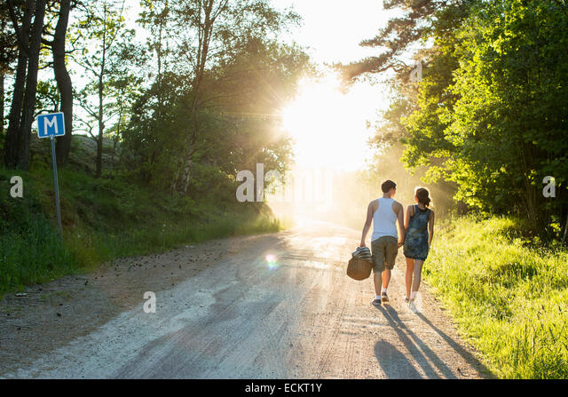 Full length rear view of couple walking on dirt road - Stock Image