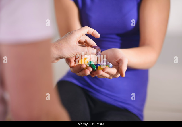 Alternative medicine, pain healing and women, young therapist choosing crystals for reiki therapy with client. Cropped - Stock Image