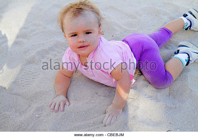 Miami Beach Florida Lummus Park baby girl crawling sand on face stuck to playing dirt bacteria health - Stock Image
