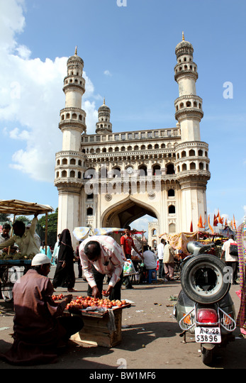 Busy street scene with people selling vegetables and with the Charminar in  background; Hyderabad India