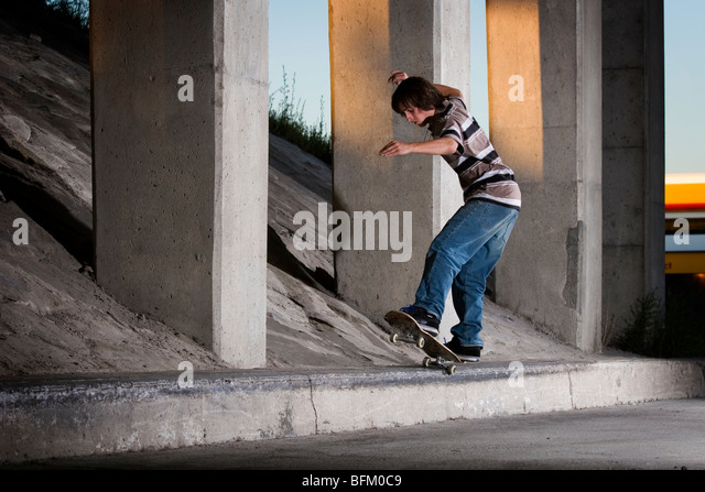 Young skateboarder doing 5-0 grind on ledge - Stock Image