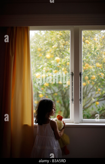 Girl aged 5 looks out window holding soft toy duck - Stock-Bilder