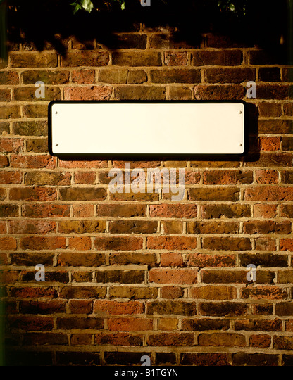 BLANK STREET SIGN ON OLD BRICK WALL - Stock Image