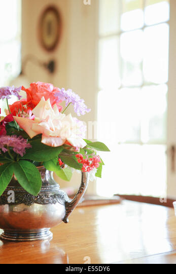Fresh flowers in antique vase on wood dining table in bed and breakfast ranch in Sonoma, California - Stock-Bilder