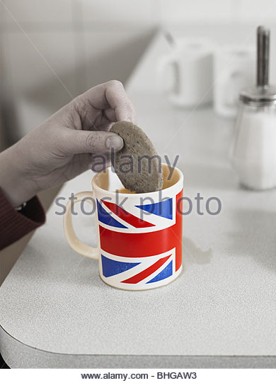 Person dipping biscuit in union jack mug of tea - Stock Image