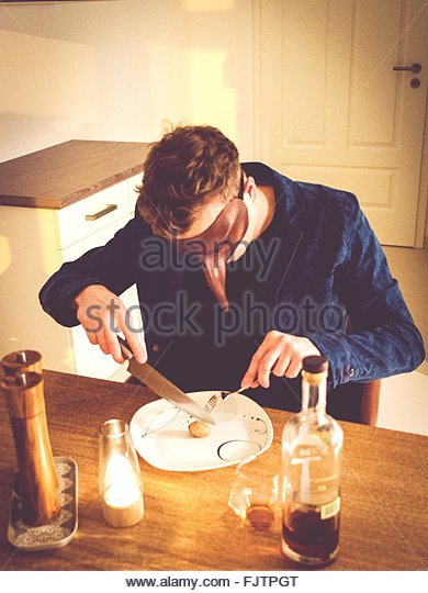 Man With Mask Eating Breakfast At Home - Stock Image