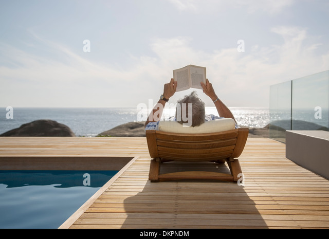 Older man reading by pool - Stock Image