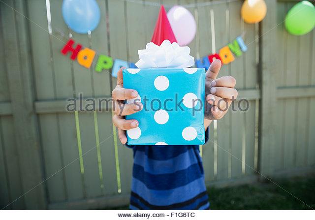 Boy holding polka-dot wrapped birthday gift - Stock Image