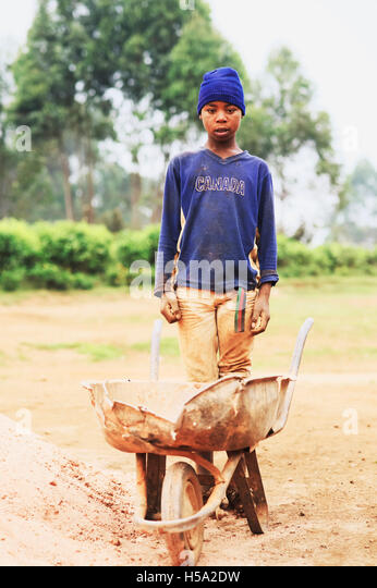 A portrait of a child worker in rural Uganda, who is working on a building site in East Africa instead of going - Stock Image