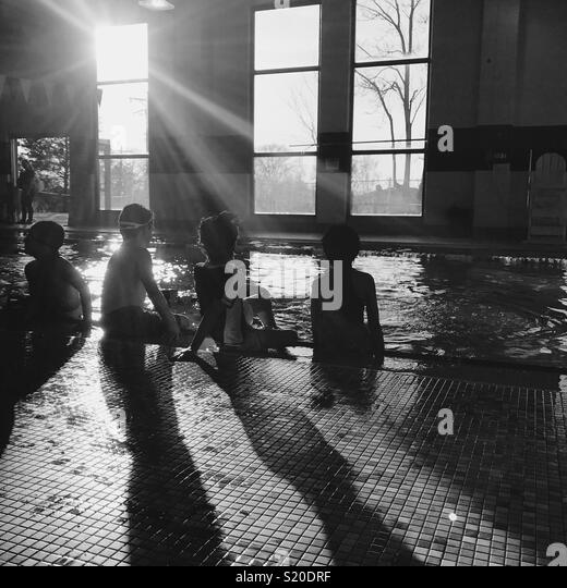 4 kids at the indoor pool in the winter. - Stock Image