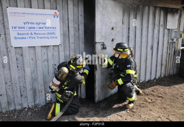 Firefighters with protective equipment prepare to enter a smoke filled room - Stock Image