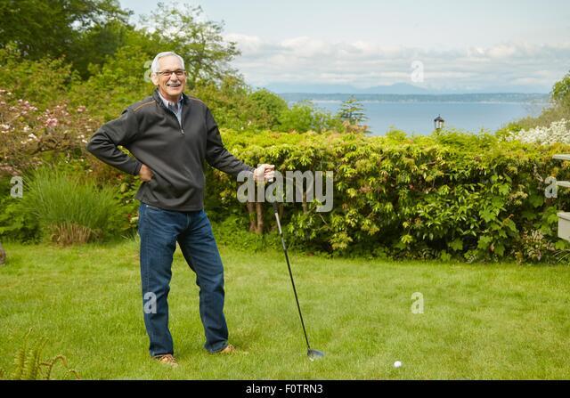 Portrait of senior man, holding golf club - Stock Image