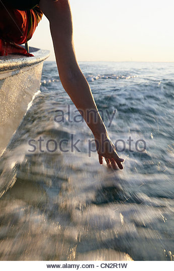 Senior woman in motorboat, hand in water - Stock Image