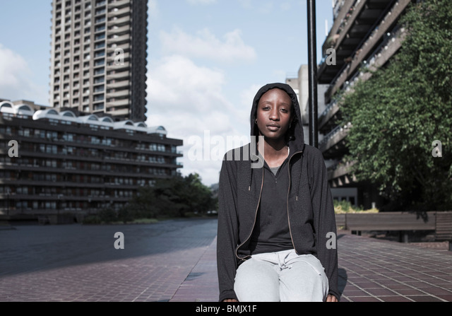 Portrait of a young woman sat outside at city housing estate - Stock-Bilder