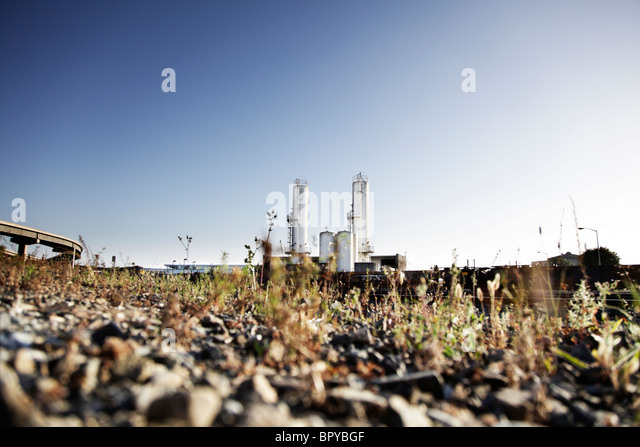 Industrial landscape with an industrial plant and highway overpass with blue sky. Low camera angle. - Stock Image