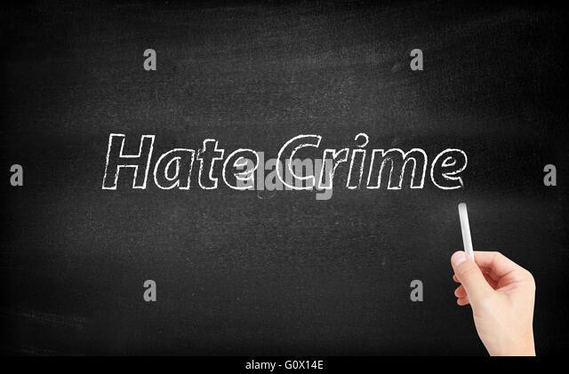Hate crime written on white blackboard - Stock Image
