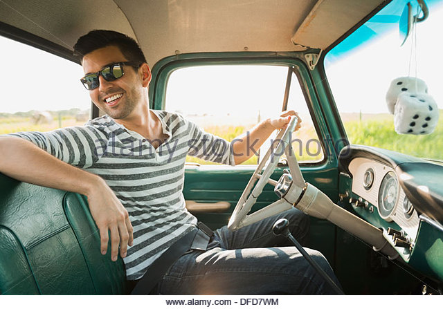 Smiling man sitting in pick-up truck - Stock Image