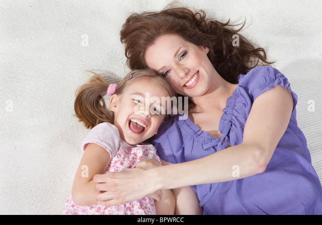Mother and daughter on rug having fun - Stock Image