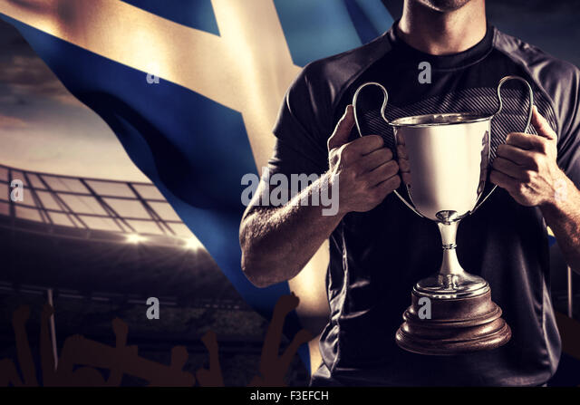 Composite image of victorious rugby player holding trophy - Stock Image