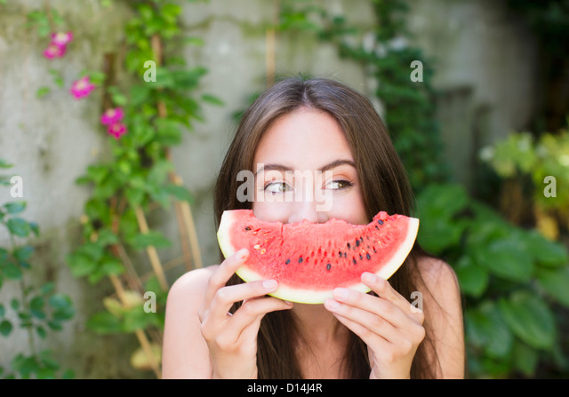 Smiling woman playing with watermelon - Stock Image