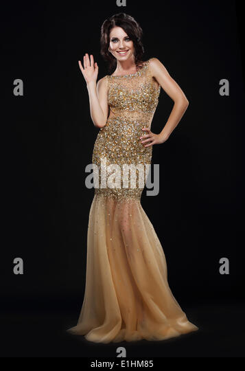 Stylishness. Well-dressed Young Woman in Long Golden Dress - Stock Image