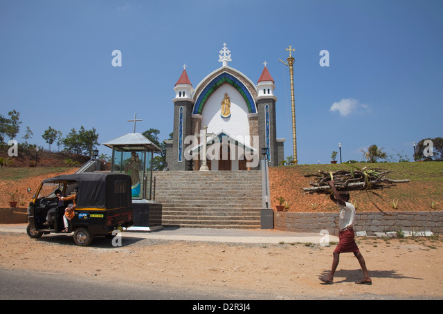 Man carrying firewood on his head walking past a church in rural Kerala, India, Asia - Stock-Bilder