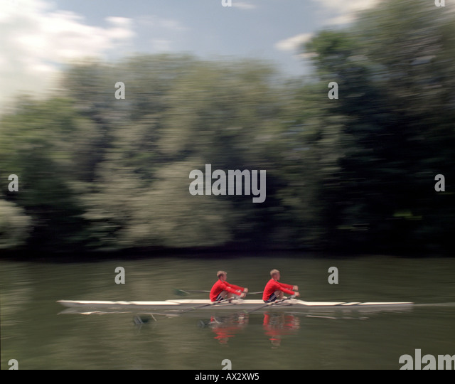 Rowing pair training on river in the summer sunshine wearing red shirts - Stock Image
