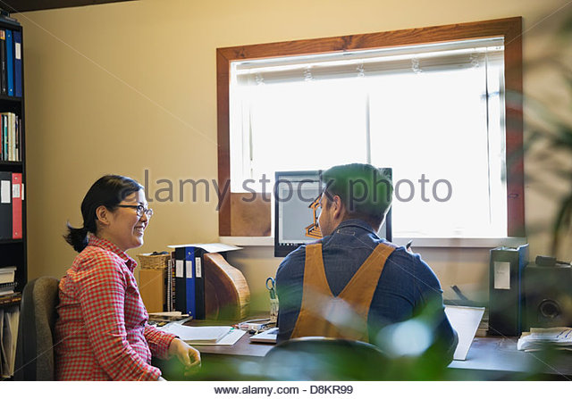 Coworkers discussing CAD drawings on computer screen - Stock-Bilder