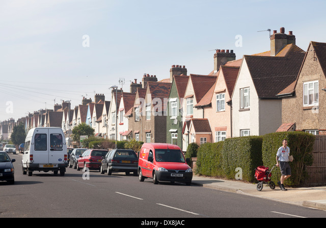 Postman delivering to suburban street of 1930's terrace houses with front gardens. - Stock Image