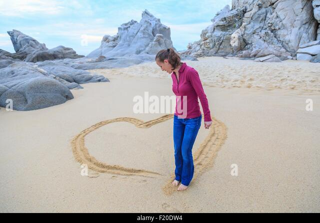 Mid adult woman on beach, drawing heart shape with feet - Stock-Bilder