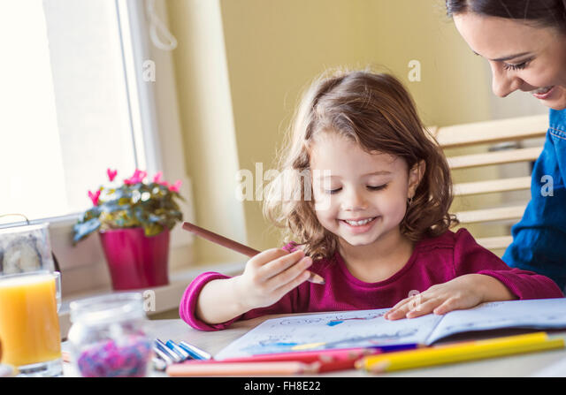 Portrait of smiling little girl painting with coloured pencils - Stock Image