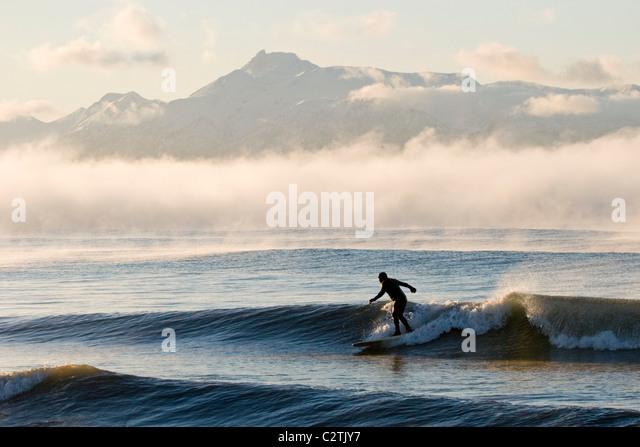 Man surfing in moring near Homer Kachemak Bay w/Kenai Mountains Kenai Peninsula Alaska Winter - Stock Image