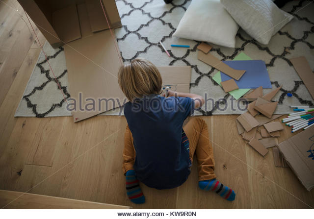 Overhead view boy coloring and cutting cardboard on living room floor - Stock Image