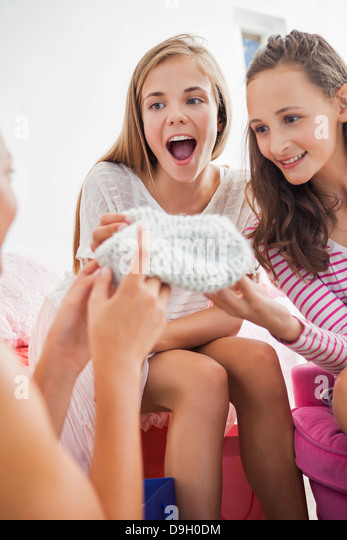 Girl showing knit hat to her friends at a slumber party - Stock Image