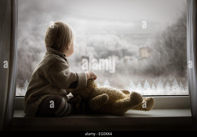 Boy sitting on windowsill with teddy bear and looking at window - Stock-Bilder