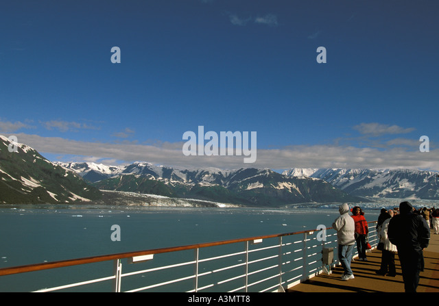 Alaska Hubbard Glacier cruise ship passengers gathered at the rail on sunny day blue sky background - Stock Image