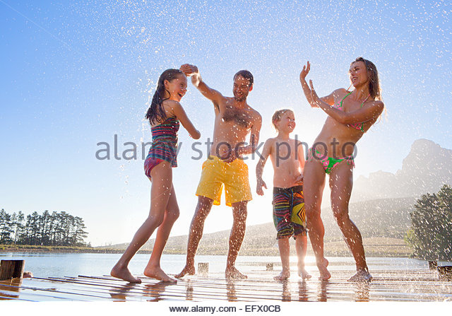 Happy family having water fight on jetty - Stock Image