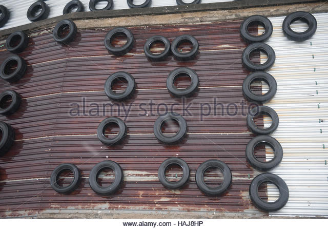 Hoi An Vietnam Corrugated iron roof in a rain shower covered in rubber tyres presumably to weigh it down in storms. - Stock Image