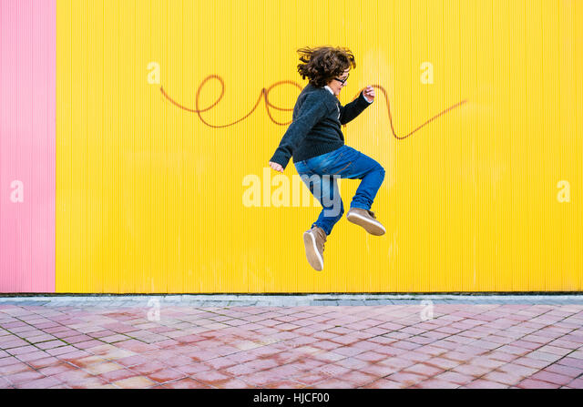 Happy boy jumping in the street. - Stock Image